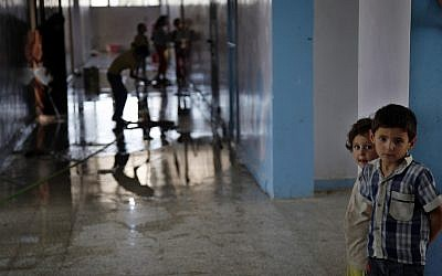 Syrian children clean a school in which they sought refuge from the fighting in Kafr Hama (six miles north of Aleppo) on Tuesday (photo credit: AP/Khalil Hamra)