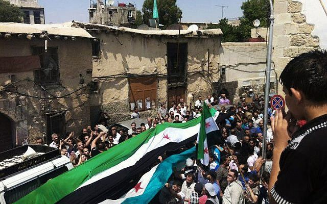 This provided by Shaam News Network, taken on Wednesday, Aug. 1, 2012, purports to show Syrians holding a large Syrian revolutionary flag during the funeral procession of Mohammed al-Naan in Damascus, Syria. (AP Photo/Shaam News Network, SNN)