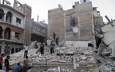 This image purports to show Syrians standing in the rubble of a destroyed building from Syrian forces shelling in Khaldiyeh neighborhood, Homs province, central Syria. (photo credit: AP/Shaam News Network, SNN)