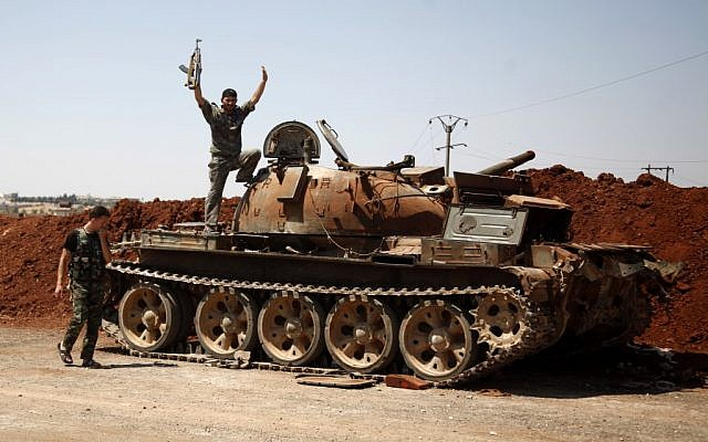 A Free Syrian Army fighter waves from the top of a destroyed army tank in the town of Anadan on the outskirts of Aleppo on Monday, Aug. 6, 2012. (photo credit: AP)