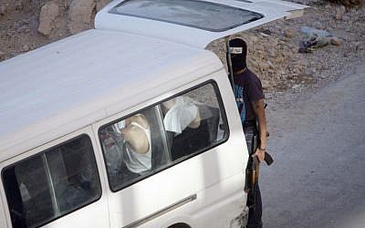 In this Thursday Aug. 2, 2012 photograph,a Syrian rebel fighter stands by a van with people detained at an improvised checkpoint in a suburb of Damascus. (photo credit: AP)