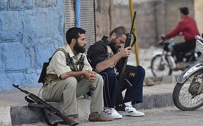 Free Syrian Army soldiers sit on a sidewalk at the northern town of Sarmada, August 1, 2012 (photo credit: AP)