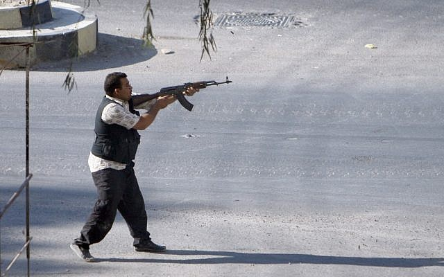 A Syrian rebel fighter fires at an approaching car at an improvised checkpoint in a suburb of Damascus, August 2 (photo credit: AP)
