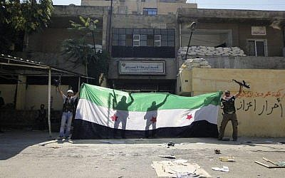 Syrian rebels celebrating after taking over the Ansari police station in the northern city of Aleppo, Syria, on August 3 (photo credit: AP)