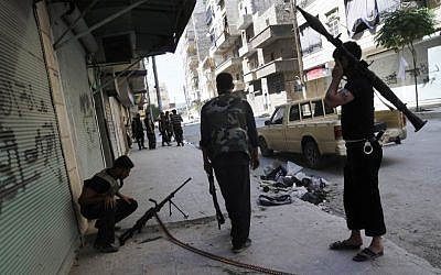 Free Syrian Army soldiers seen during clashes with government forces in the southwest district of Salah al-Din in Aleppo, Syria last week. The fighting in Aleppo, Syria's largest city, has raged for more than 2 weeks. (photo credit: Alberto Prieto/AP)