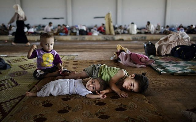 Syrian children, who fled their home with their family, lie on the ground, while they and others take refuge at the Bab Al-Salameh border crossing, in hopes of entering one of the refugee camps in Turkey, near the Syrian town of Azaz, Sunday, Aug. 26, 2012. (photo credit: Muhammed Muheisen/AP)