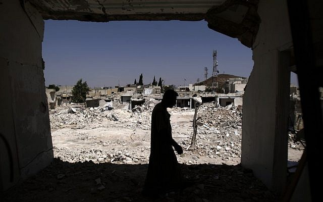 A Syrian man walks in his house, which was destroyed in a Syrian government forces shelling, over looking the rubble of other houses, in Azaz, on the outskirts of Aleppo, Syria, Wednesday, Aug. 29, 2012. (photo credit: Muhammed Muheisen/AP)