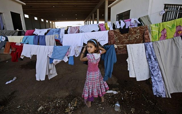 A Syrian girl who fled her home with her family checks her laundry as she and others take refuge at the Bab Al-Salameh border crossing with Turkey, near the Syrian town of Azaz, on Sunday, Aug. 26, 2012. (photo credit: Muhammed Muheisen,/AP