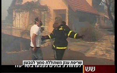 Firefighters work to extinguish a fire raging in Kiryat Tivon on Thursday. (photo credit: Image capture from Channel 2)