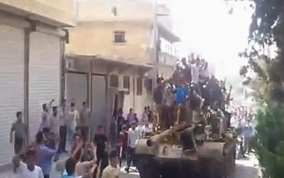 Free Syrian Army troops riding through Al Bab on a captured Syrian army tank. (photo credit: Image capture from YouTube)