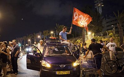 A demonstrator waves a flag at one of two protests Saturday night in Tel Aviv (photo credit: Tali Mayer /Flash90)