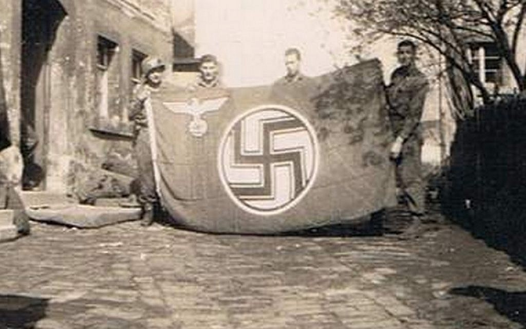 The author's father, Private Alexander Breuer (left), holding a Nazi flag he captured with his comrades in a small German town (photo credit: courtesy Heddy Abramowitz)