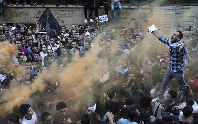 Protesters chant slogans amid orange smoke outside the US embassy in Cairo last week (photo credit: Mohammed Abu Zaid/AP)