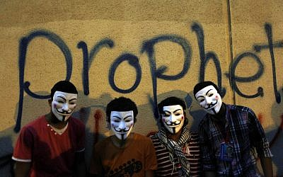 Egyptian protesters wearing Guy Fawkes masks pose for a photo in front of graffiti on a wall of the US Embassy during a protest in Cairo, Egypt, Tuesday, September 11, 2012 (photo credit: Nasser Nasser/AP)