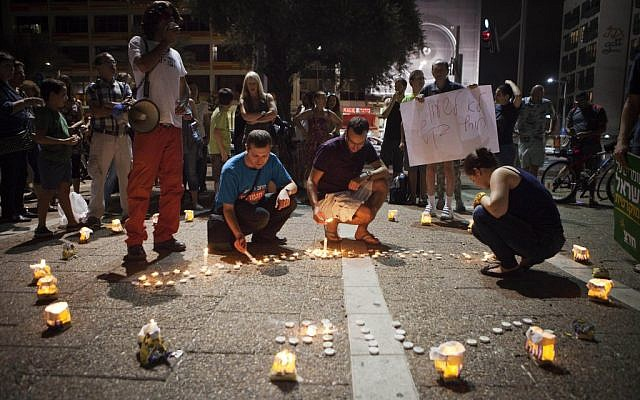 Israelis light candles in the shape of a clock during a protest against the government decision to return to winter clock more than a month ahead of Europe and the US in Tel Aviv, Saturday, September 22, 2012 (photo credit: AP/Dan Balilty)
