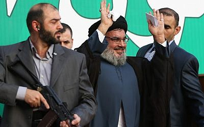 Hezbollah leader Hassan Nasrallah, center, escorted by his bodyguards, waves to a crowd of hundreds of thousands of supporters in Beirut, Lebanon in September, 2012. (Illustrative photo credit: AP/Hussein Malla)