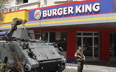 Lebanese soldiers guarding a Burger King in Sidon on Saturday, after two other fast food places in the country were torched. (photo credit: AP/Mohammed Zaatari)