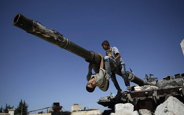 Children play on a Syrian tank destroyed during fighting in the Syrian town of Azaz, on the outskirts of Aleppo, September 2, 2012 (photo credit: AP/Muhammed Muheisen)