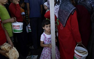 A Syrian girl who fled her home due to fighting between the Syrian army and the rebels waits her turn to buy bread and eggs near a border crossing with Turkey, on Monday, September 3 (photo credit: AP/Muhammed Muheisen)