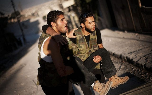 Two Free Syrian Army fighter evacuate a wounded comrade in Aleppo, September 7 (photo credit: AP/Manu Brabo)