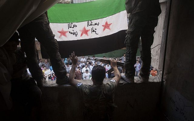 Members of the Free Syrian Army hold up a revolutionary flag in Aleppo, September 21 (photo credit: AP Photo/ Manu Brabo)