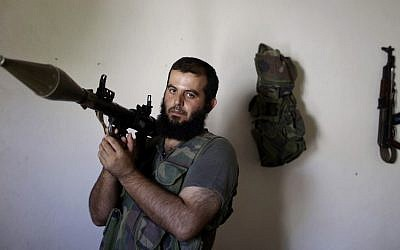 In this Tuesday, Sept. 4, 2012, photo, Syrian rebel fighter, Abu Muslim, 30, a former librarian, poses for a picture at a house where he and others wait their turn to go and fight against government forces in Aleppo, in Marea on the outskirts of Aleppo.(AP Photo/Muhammed Muheisen)