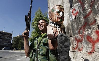 A Free Syrian Army soldier holds up a bust of Hafez Assad tied to a shoe, a symbol of humiliation in Aleppo, September 24 (photo credit: AP/Hussein Malla)