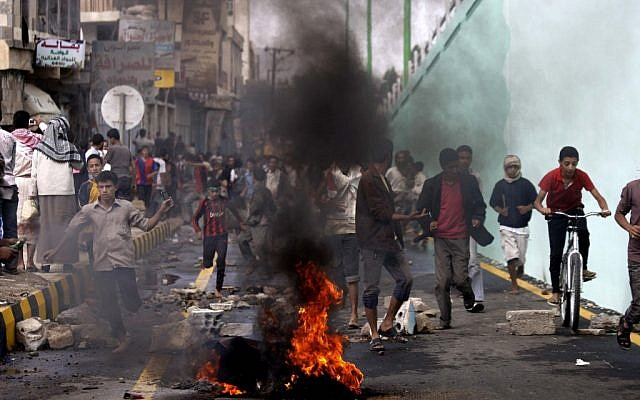Protesters run as police, unseen, open fire into the air near the US Embassy during a protest about a film ridiculing Islam's Prophet Muhammad, in Sanaa, Yemen, Thursday, Sept. 13, 2012. (photo credit: Hani Mohammed/AP)