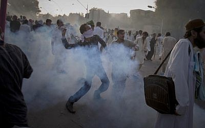 A Pakistani protester hurls back a tear gas canister fired by police during clashes that erupted as the demonstrators tried to approach the US embassy in Islamabad, Pakistan. (AP Photo/Anjum Naveed)