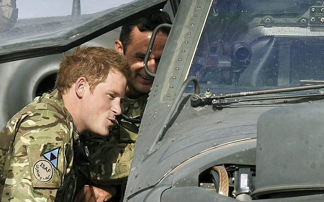 Great Britain's Prince Harry examines the cockpit of an Apache attack helicopter at Camp Bastion in Afghanistan in early September. (photo credit: AP/John Stillwell)