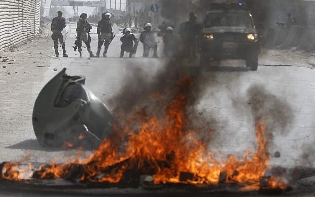 Afghan police stand by burning tires Monday in Kabul during violent protests against the anti-Islam film that ridicules the Muslim Prophet Muhammad. (photo credit: AP Photo/Ahmad Jamshid)
