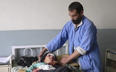 An Afghan woman is treated for injuries sustained during a NATO airstrike, which followed a daring Taliban raid on one of its facilities. (photo credit: Khalid Khan/AP)