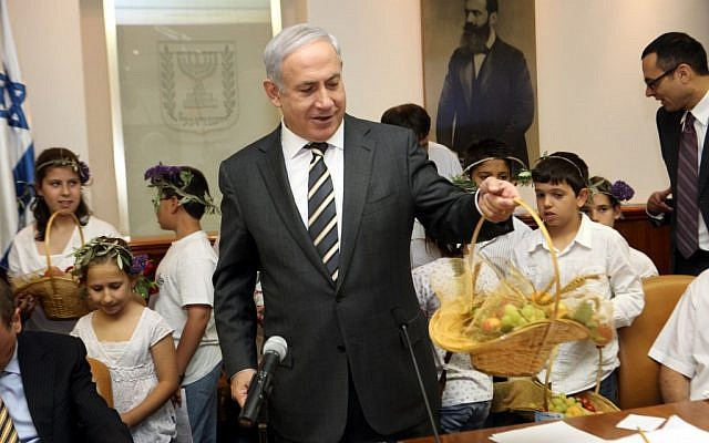 Netanyahu with a fruit basket during the holiday of Shavuot.  This season has seen a spike in Israelis requesting help from food organizations (photo credit: Yossi Zamir/Flash90)