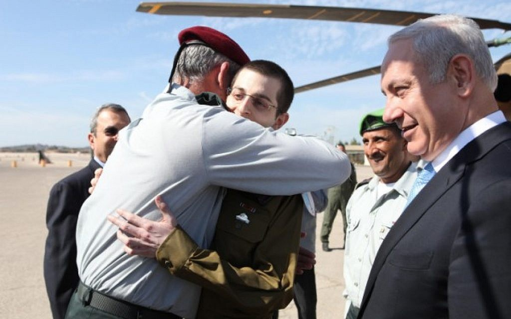 Lt. Gen. Benny Gantz hugging Gilad Shalit on the day of his release from Hamas captivity, October 18, 2011, as Ehud Barak and Benjamin Netanyahu look on. (IDF Spokesperson/ Flash 90)