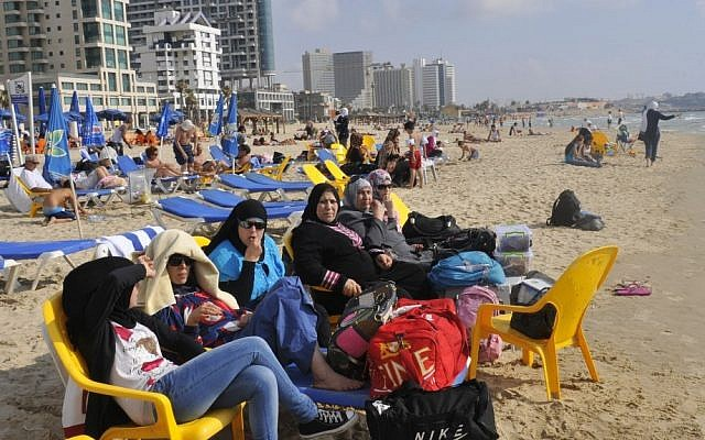 Young Arab women sit on the beach in Tel Aviv earlier this year (photo credit: Serge Attal/Flash90)