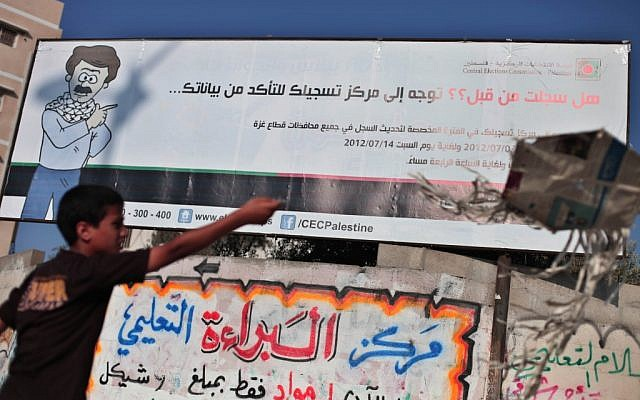 A Palestinian next to an elections billboard in Gaza. (photo credit: Wissam Nassar/Flash90)
