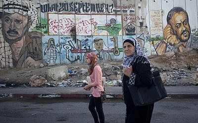 Palestinian women pass by a mural depicting late Palestinian Authority president Yasser Arafat and jailed Tanzim leader Marwan Barghouti at the Qalandiya checkpoint. (Yonatan Sindel/Flash90)