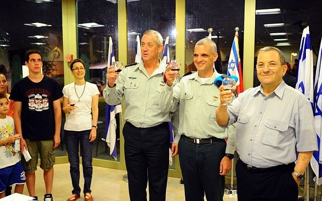 Yoav Har-Even (center) lifts a glass with IDF Chief of Staff Benny Gantz (left) and Defence Minister Ehud Barak after being promoted last week. Har-Even, whose family is at left, was named Tuesday to head the IDF's Operations Division. (Photo credit: Ori Shifrin/IDF Spokesperson/Flash90)