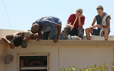 Settler youth atop a trailer home in the settlement of Migron on Sunday. (photo credit: Oren Nahshon/Flash90)