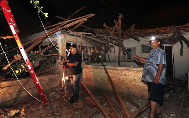 Men inspect damage to a house in Netivot that was hit by long-range Grad rocket fired from the Gaza Strip, Sunday Sep. 9 (photo credit: Tsafrir Abayov/Flash90)