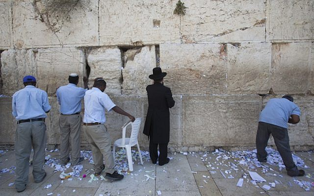 Workers remove thousands of notes and letters from the Western Wall ahead of the new year (photo credit: Yonatan Sindel/Flash90)