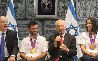 Medalists Noam Gershony (gold, tennis) and Inbal Pezaro (bronze, swimming) with President Shimon Peres and Prime Minister Benjamin Netanyahu at a welcoming ceremony for the Paralympic team at the President's Residence in Jerusalem, in September 2012. (photo credit: Flash90/Miriam Alster)