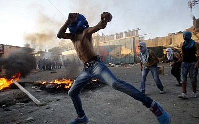 In scenes reminiscent of the first intifada, masked Palestinians throw stones towards Israeli security forces in the Shuafat refugee camp on the outskirts of Jerusalem in September (photo credit: Suliman Khader/Flash90)