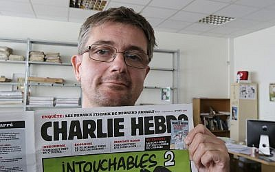 Publishing director of the satyric weekly Charlie Hebdo, Charb, displays the front page of the newspaper as he poses for photographers in Paris, Wednesday, Sept. 19, 2012. (photo credit: AP/MIchel Euler)