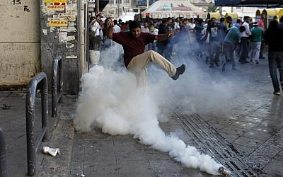A man tries to kick a tear-gas canister away, as Muslims protest in Athens against a film produced in the U.S. that they say insults the Prophet Muhammad on Sunday. (photo credit: AP/Kostas Tsironis)