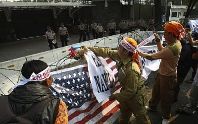 Police officers watch as Muslim protesters hang banners and a US flag on the razor wire surrounding the US Embassy compound in Jakarta, Indonesia, September 19, 2012 (photo credit: AP/Tatan Syuflana)