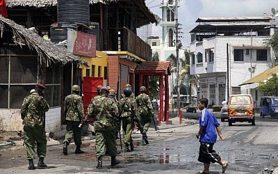 Kenyan Paramilitary soldiers patrol after clearing the area of Muslim youths who were shouting slogans of 'Allah Akbar', God is Great, after the Friday prayers outside the Musa Mosque in the Majengo suburb of Mombasa Kenya, Friday. (photo credit: AP)