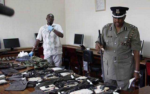 A Kenya Police spokesman displays arms and ammunition seized in Nairobi, Kenya, Friday, Sep. 14 (photo credit: AP/Khalil Senosi)