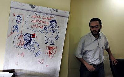 """Egyptian cartoonist Abdul-Rahman Najmuddin walks past cartoon sketches, one depicting Egyptian president Mohammed Morsi with a caption in Arabic """"someone calls home and tell them that I am delivering a speech,"""" at Al Watan daily newspaper headquarters in Cairo on Wednesday. (photo credit: AP/Nasser Nasser)"""