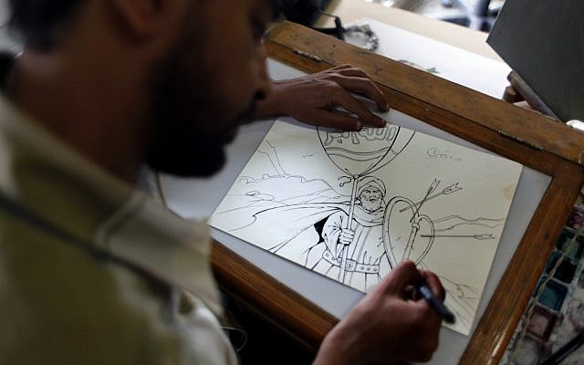 Egyptian cartoonist Khalid Abdul-Ati from the Egyptian Al Watan daily newspaper works on a cartoon depicting an Islamic figure inside his office at the newspaper's headquarters in Cairo on Wednesday. (photo credit: AP/Nasser Nasser)